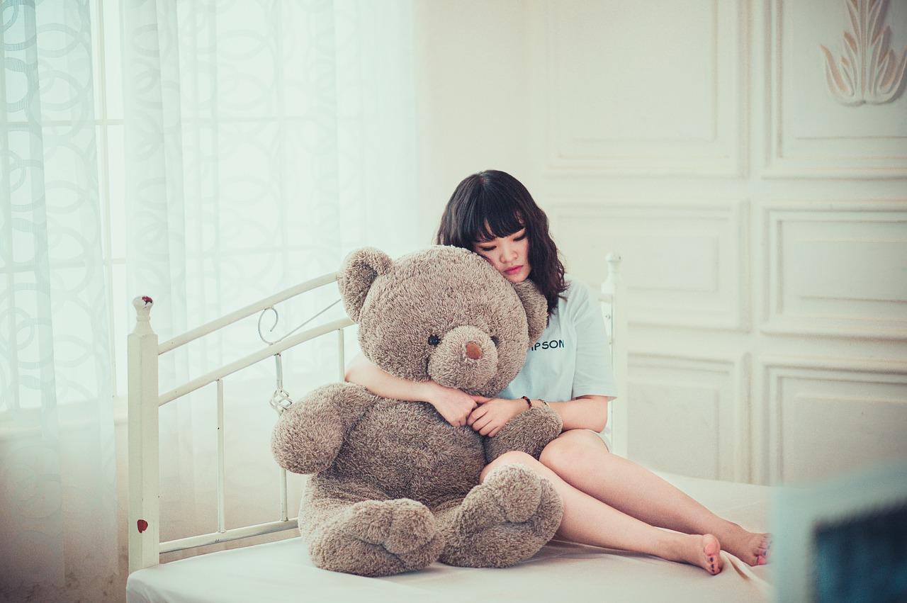 נערה על המיטה עם דובי